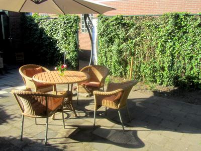 Foto van het grote privé terras met tuinset en parasol
